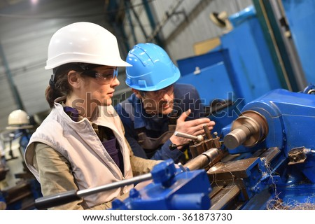 Metal worker teaching trainee on machine use - stock photo