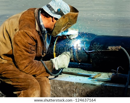 Metal worker welds two pieces of metal together - stock photo