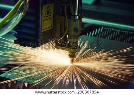 metal working. Laser cutting technology of flat sheet metal steel material processing with sparks. Authentic shooting in challenging conditions. Maybe little blurred. - stock photo