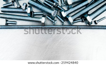 Metal working tools. Metal style. Hairpin and other fixing elements on the scratched metal background. - stock photo