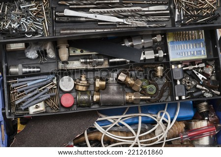 Metal workshop. Plastic toolbox with screws, bolts and some tools. - stock photo