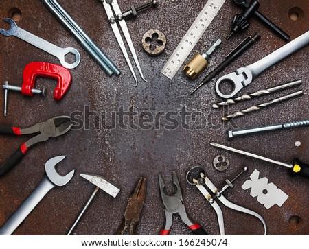 Metal workshop tools on old metal background - stock photo