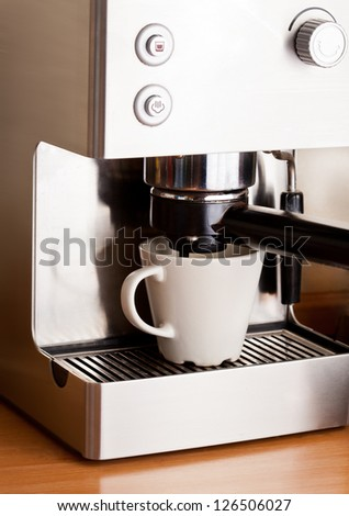 Metall coffee machine and cup of fresh coffee with foam