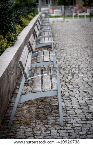 Metallic and wooden bench in a row, detail