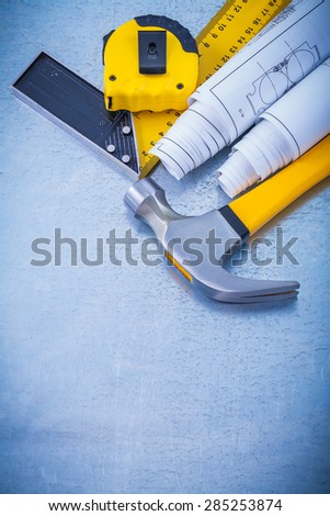 Metallic background with blueprints claw hammer square ruler and measuring line maintenance concept