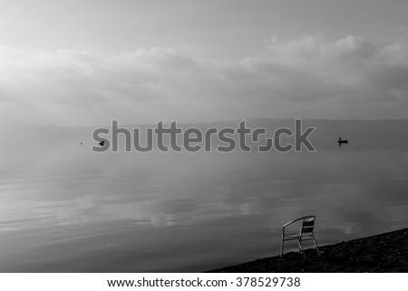 Metallic chair, buoy and boat at lake - stock photo