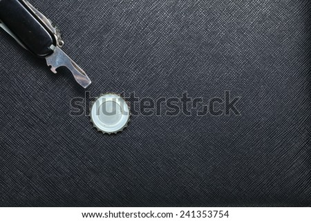 Metallic crown cap beside bottle opener in utility knife set put on black color leather surface background represent the beverage containing equipment - stock photo