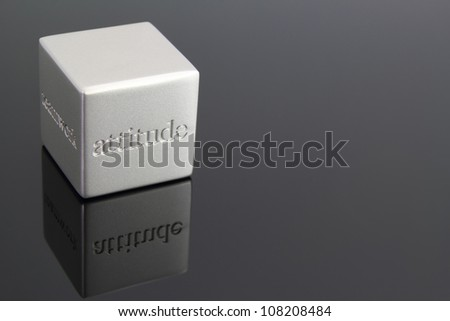 "Metallic cube paperweight with the word ""attitude"" engraved in the side. - stock photo"