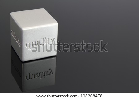 "Metallic cube paperweight with the word ""quality"" etched in the side. - stock photo"