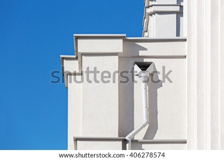 metallic drain pipe on grey plaster wall of building - stock photo
