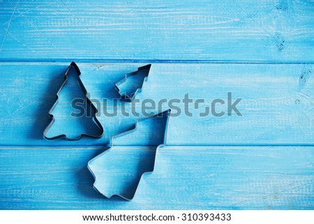 metallic forms for the preparation of christmas cookies on a blue wooden background. christmas ideas. copy space for you text
