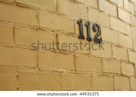 metallic house numbers against cream brick wall - stock photo