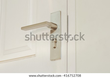 metallic knob on white door horizontal - stock photo
