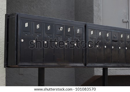metallic mailbox array tidy infront of apartment houses - stock photo