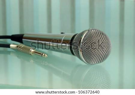 Metallic microphone on a striped transparent surface taken closeup.