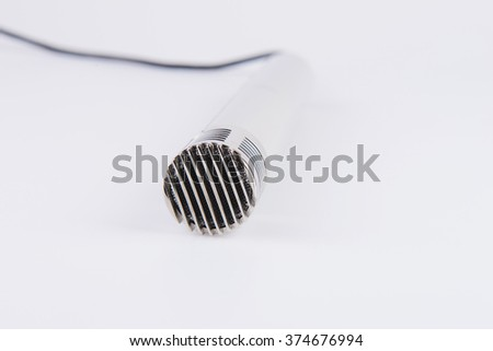 metallic microphone with wire on white - stock photo
