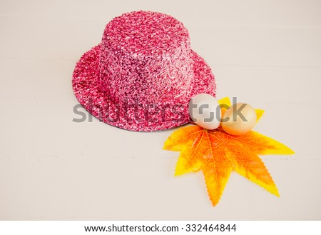 Metallic pink party hat with egg painting to decorate for the party. - stock photo