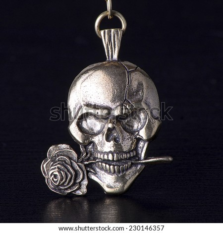 Metallic skull with rose isolated on black background, trinket of bronze.