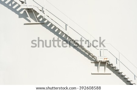 metallic staircase floating on an off-white wall background - stock photo