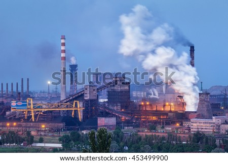 Metallurgical plant with white smoke at night. Steel factory with smokestacks . Steelworks, iron works. Heavy industry. Air pollution from smokestacks, ecology problems. Industrial landscape - stock photo