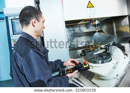 metalwork industry. worker operating cnc milling machine center in tool manufacture workshop - stock photo