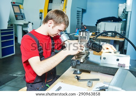 metalwork. worker in uniform checking quality of processed tool using precise optical device
