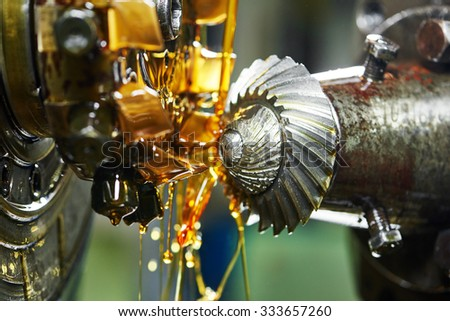 metalworking industry: conic tooth gear wheel machining by hob cutter mill tool. Selective focus on teeth. - stock photo