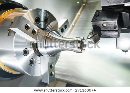 metalworking  industry: cutting steel metal shaft processing on lathe machine in workshop. Selective focus on tool - stock photo