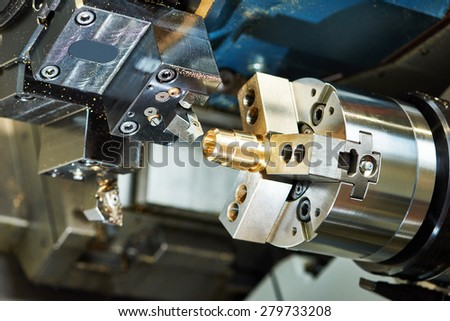 metalworking  industry: cutting tool processing bronze metal detail on lathe machine in factory workshop - stock photo