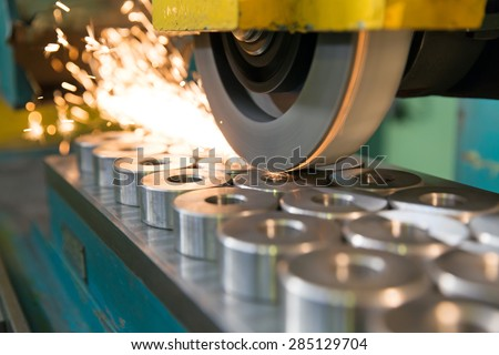 metalworking industry: finishing metal working on horizontal surface grinder machine with flying sparks - stock photo
