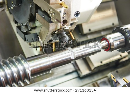 metalworking  industry: mill cutting tool ready to process steel metal shaft on lathe machine in workshop - stock photo
