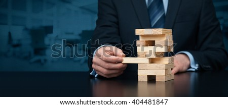 Metaphor of risk in business. Risk management concept. Businessman remove one piece from tower, wide banner composition with office in background. Nothing ventured, nothing gained.
