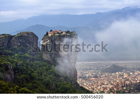 Meteora monasteries. Beautiful view on Monastery of the Holy Trinity placed on the edge of high rock covered of the morning mist and clouds at sun rises, Kastraki, Greece