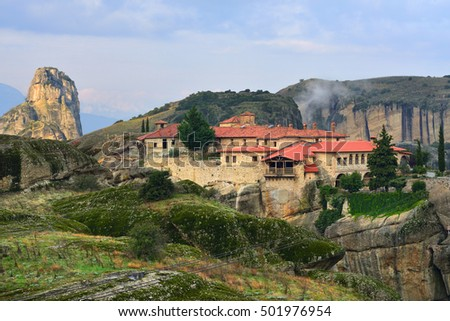 Meteora monasteries. Beautiful view on Monastery of the Holy Trinity placed on the edge of high rock illuminated of the first morning sun rays, Kastraki, Greece