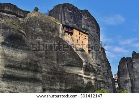 Meteora monasteries. Beautiful view on the Holy Monastery of St Nikolaos Anapafsas placed on the edge of high rock at sunset light, Kastraki, Greece