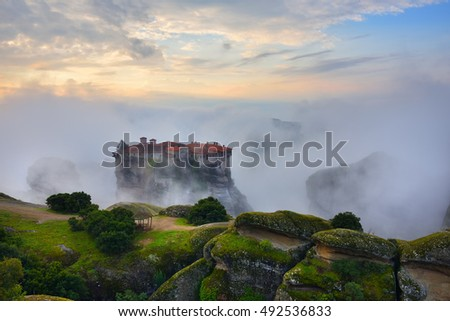 Meteora monasteries. Beautiful view on the Holy Monastery of Varlaam placed on the edge of high rock covered of the morning clouds and mist at sunrise, Kastraki, Greece