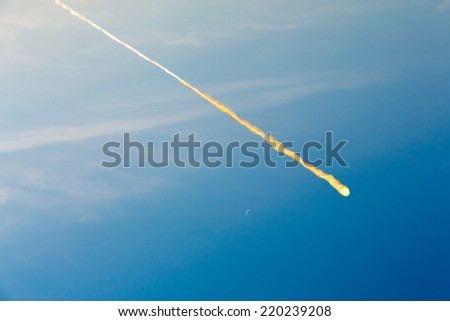 meteorite falling on the blue sky background (collage) - stock photo