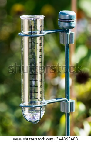 Meteorology with a rain gauge in the garden - stock photo