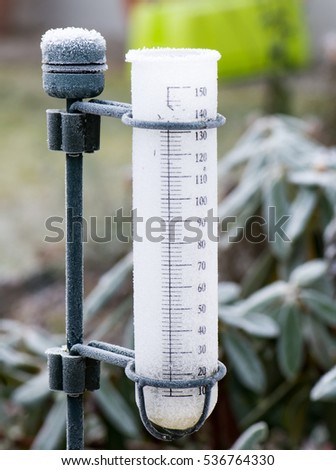 Meteorology with a rain gauge in the garden - frozen after a cold night