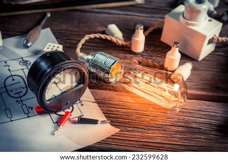 Meter and electric light bulb in the laboratory - stock photo