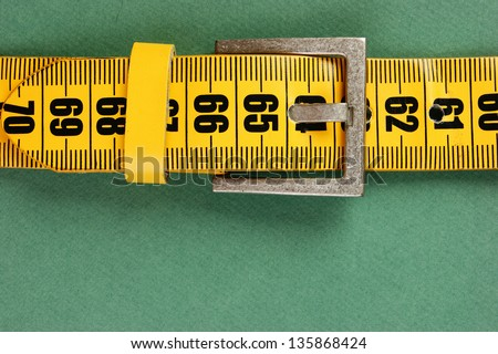 meter belt slimming on the green background - stock photo
