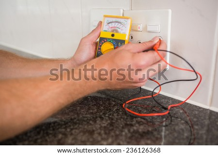 Metering voltage with digital multimeter in the kitchen - stock photo