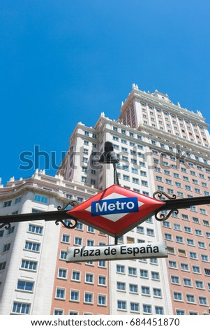 Metro entrance sign at Plaza de Espana in Madrid, Spain with the famous Edificio Espana in the background.