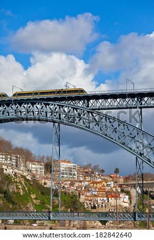 Metro Train on the Bridge of Dom Luiz in Porto. Vertical shot - stock photo