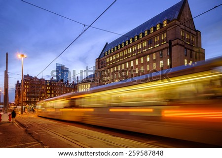 Metro tram passing in front of the new extension of the Manchester town hall, Manchester, England. - stock photo