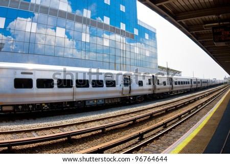 Metropolitan commuter train passing through the station with sky reflected in building behind. - stock photo