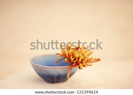 Metta or Lovingkindness. Photograph of a simple hand crafted ceramic bowl with a flower. - stock photo