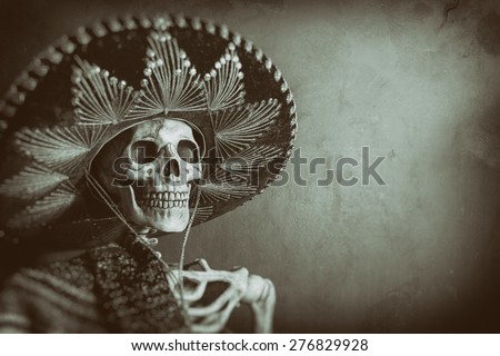 Mexican Bandit Skeleton 7. A skeleton wearing a Mexican sombrero and a poncho. Edited in a vintage film style. - stock photo