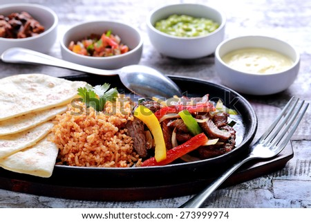 mexican beef fajitas served with rice, soft flour tortillas at hot plate and four different sauces - stock photo