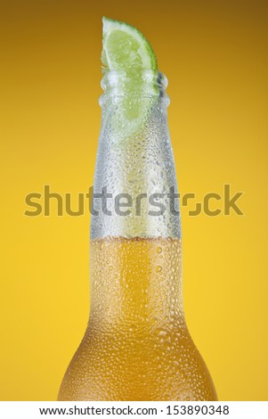 Mexican beer with a lime slice over a yellow background.